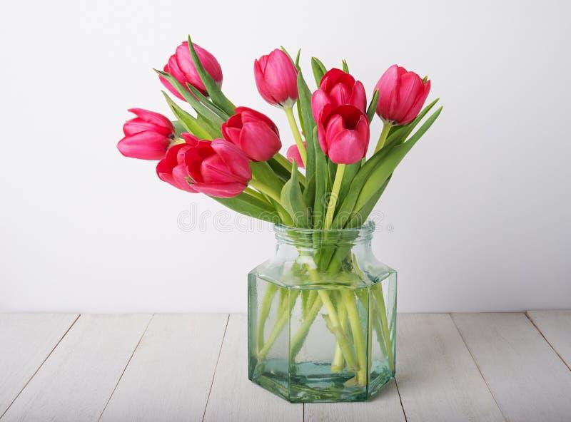 Bündel der roten Tulpe blüht in einem Glasweinleseglas lizenzfreies stockbild