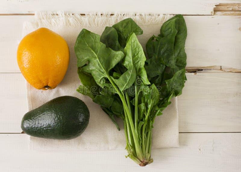 Bündel des frischen Spinats, der Orange und der Avocado auf weißem hölzernem backg stockfotografie