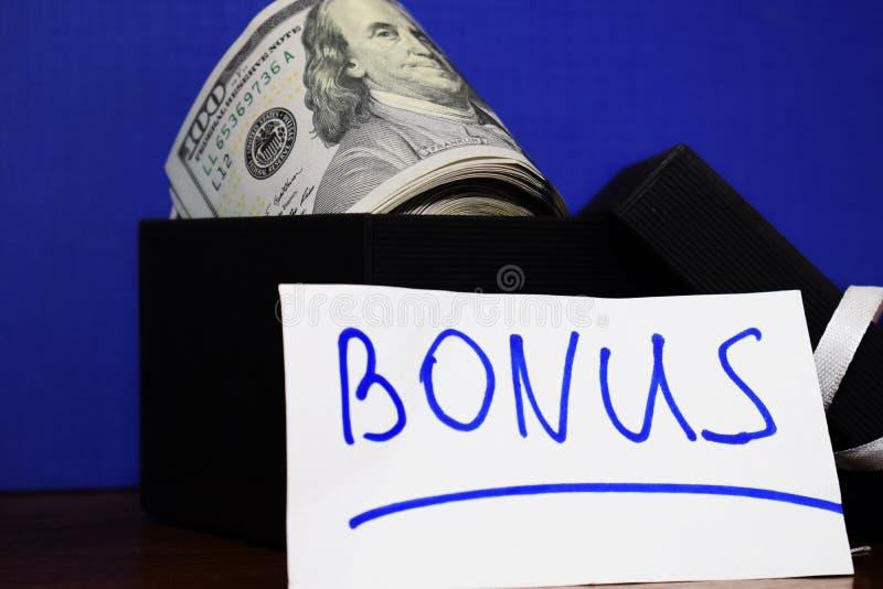 Bündel Dollar in der Geschenkbox lokalisiert auf blauem Hintergrund, die Aufschrift Prämie stockbilder