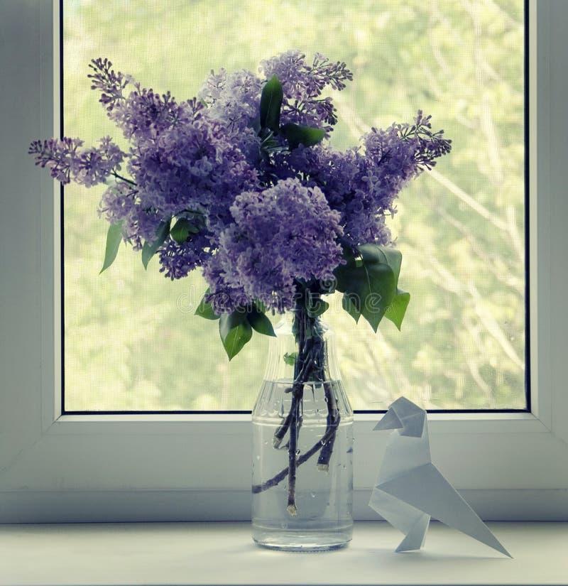 Bündel Fliedern auf einem Fensterbrett und Origamizahl eines Raben stockbilder