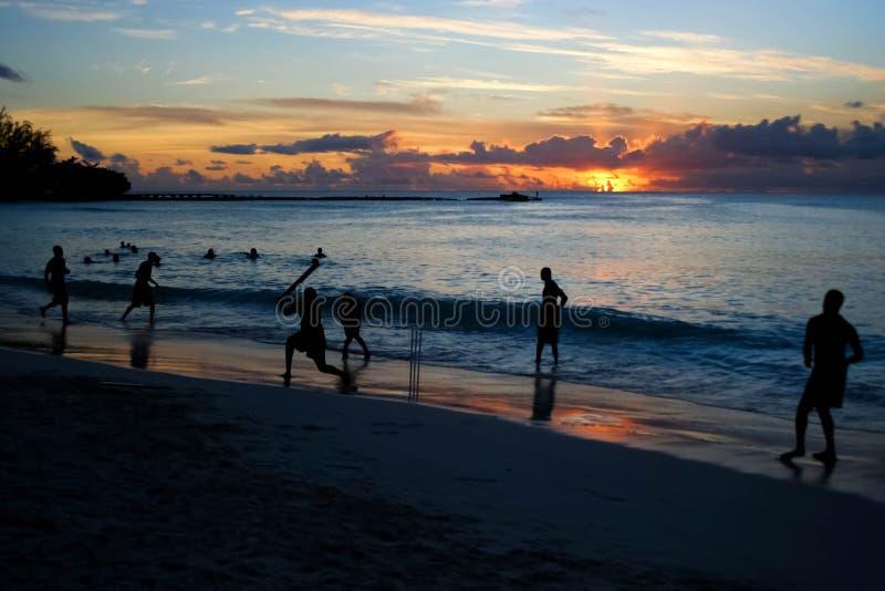 Bündel Freunde, die Kricket am Strand in Barbados spielen lizenzfreies stockfoto