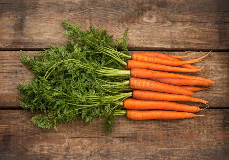 Bündel frische Karotten über hölzernem Hintergrund lizenzfreies stockfoto