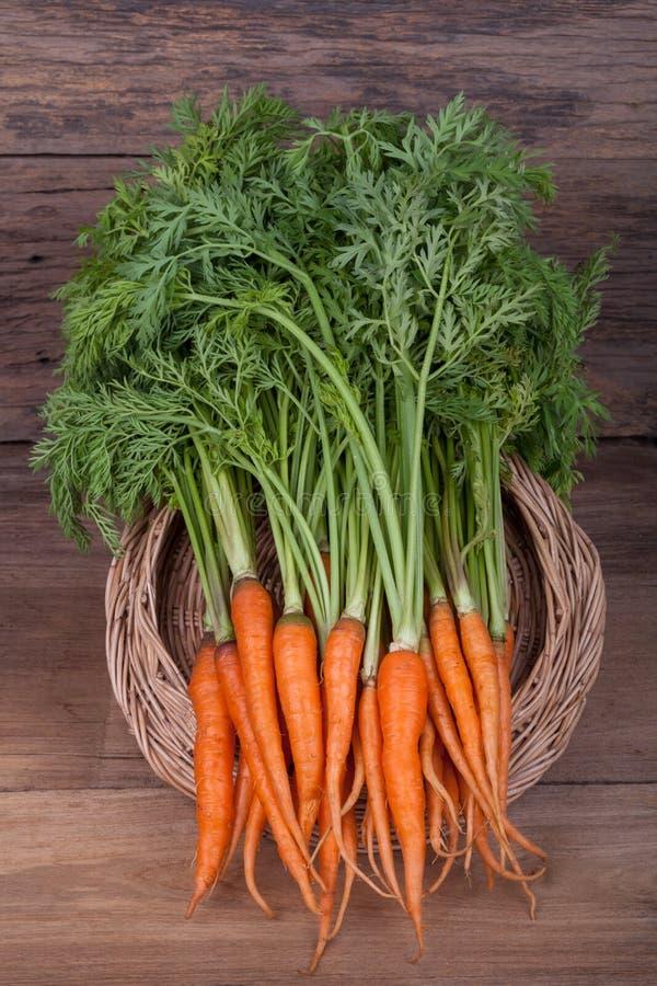 Bündel frische Karotten mit Grün verlässt über hölzernem Hintergrund lizenzfreies stockbild