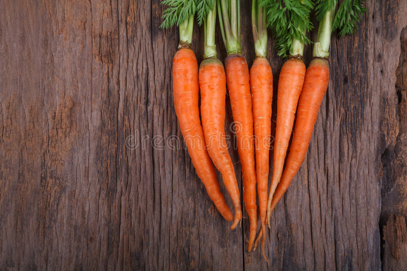 Bündel frische Karotten mit Grün verlässt über hölzernem Hintergrund lizenzfreie stockbilder