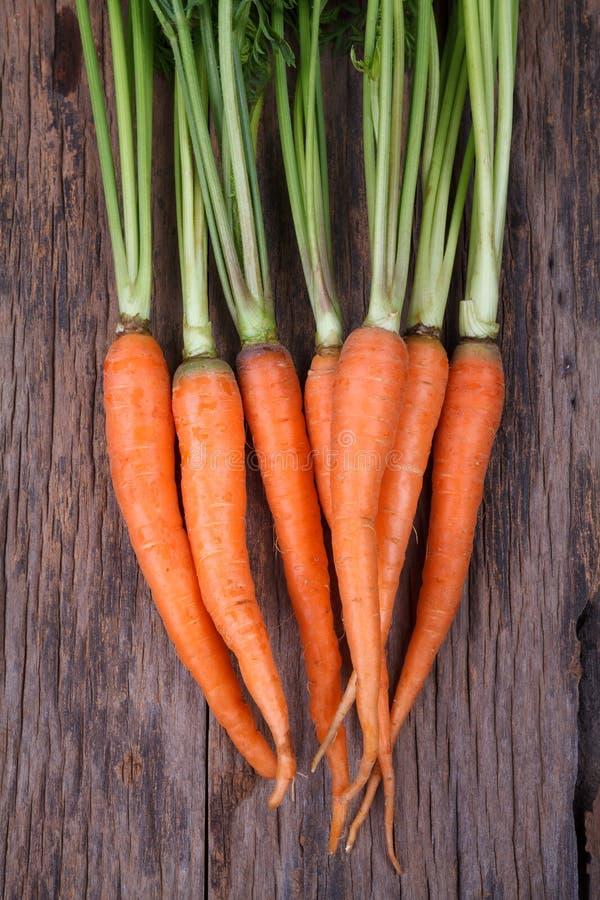 Bündel frische Karotten mit Grün verlässt über hölzernem Hintergrund stockfotografie
