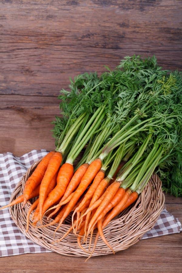 Bündel frische Karotten mit Grün verlässt über hölzernem Hintergrund stockfotos