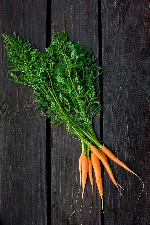 Bündel frische Karotten mit Grün verlässt über hölzernem Hintergrund stockfoto