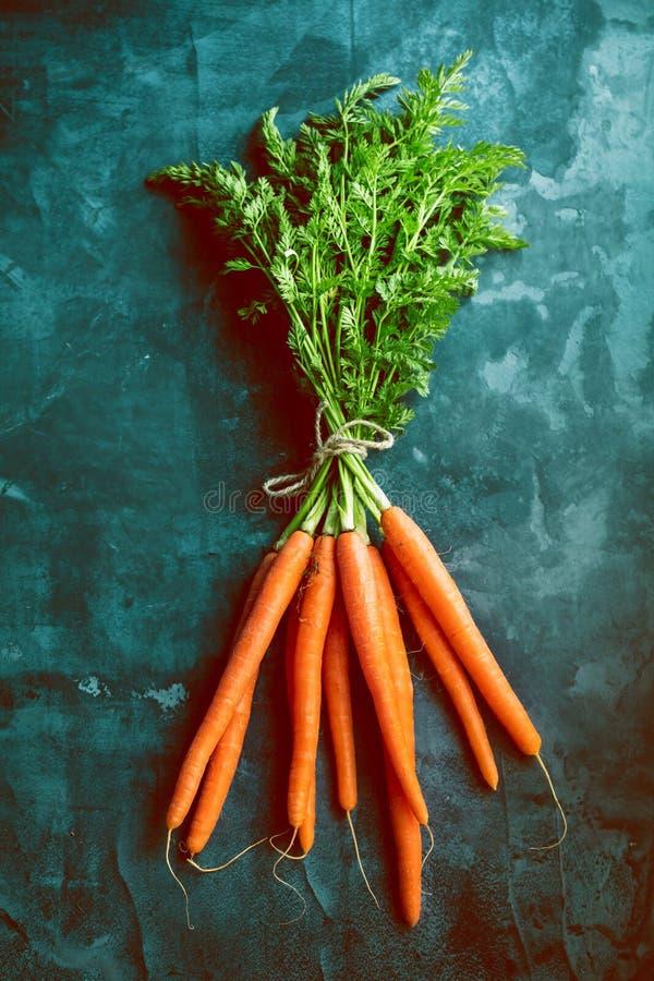 Bündel frische Karotten mit grünen Blättern über beton Hintergrund gemüse Nahrung stockbilder