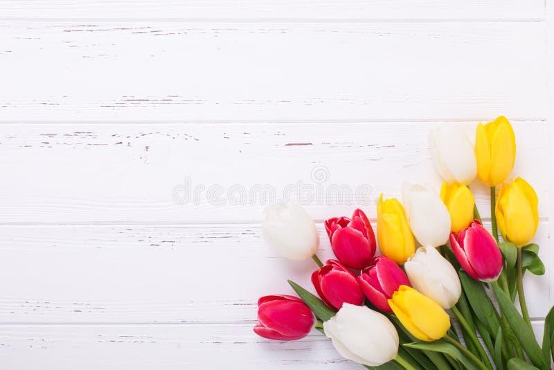 Bündel gelbe, rote und weiße Tulpen blüht auf der hölzernen Weinlese lizenzfreie stockfotos