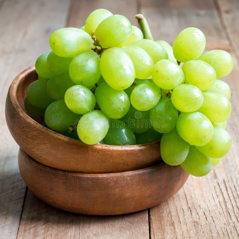 Bündel grüne reife Trauben in der hölzernen Schüssel, Quadrat lizenzfreies stockfoto