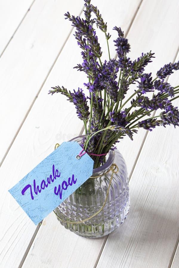 Bündel Lavendel in einem Glaslaternenglas, mit danken Ihnen geschrieben auf einen blauen Geschenkaufkleber lizenzfreie stockbilder