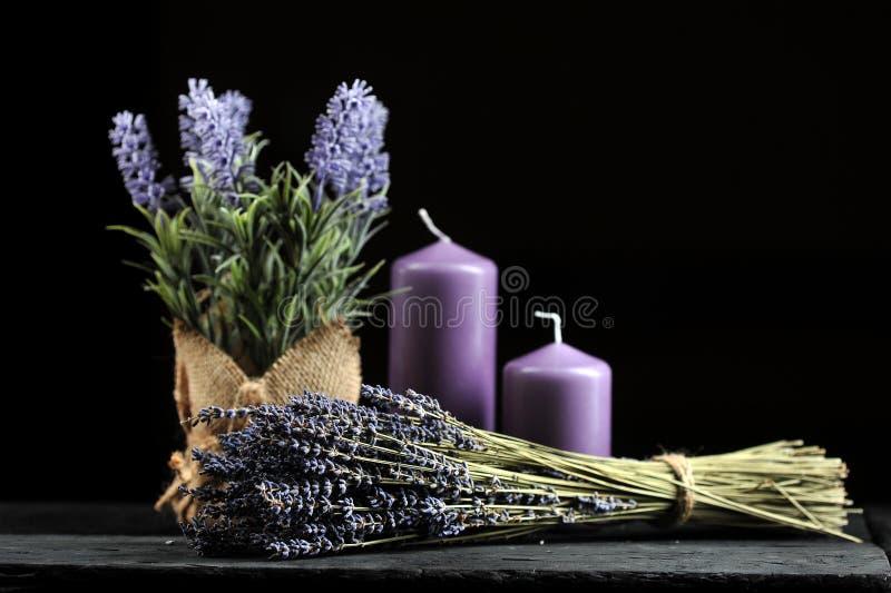 Bündel Lavendel gebunden mit Schnur und aromatischen lila Kerzen lizenzfreie stockfotos
