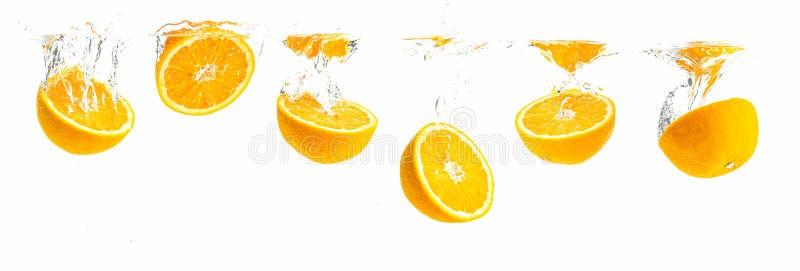 Bündel organische orange Hälften, die in haarscharfes Wasser mit Luftblasen sinken Panoramische Ansicht stockbilder
