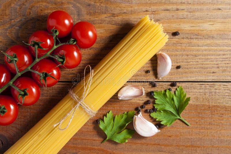 Bündel rohe Spaghettis gebunden mit Seil, Tomaten Kirsche, Scheiben des Knoblauchs, Petersilienblättern und Pfeffer auf braunem h lizenzfreies stockfoto