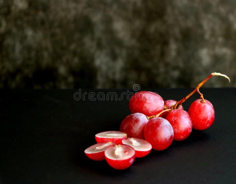 Bündel rosa Trauben auf einem schwarzen Hintergrund lizenzfreie stockfotos