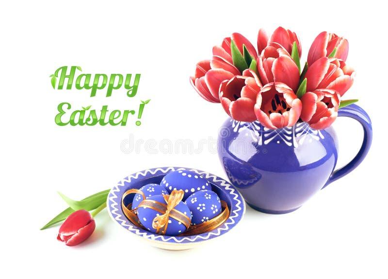 Bündel rote Tulpen im blauem keramischem Vase und in Ostereiern im Mach lizenzfreie stockbilder