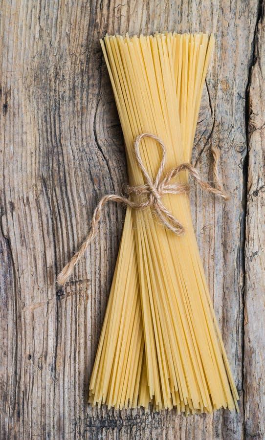 Bündel Spaghettis auf einem Holztisch stockfotos