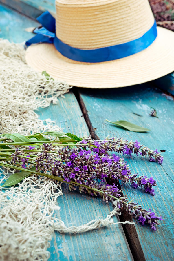 Bündel von Lavendelblumen, -Fischernetz und -strohhut auf dem blauen Weinleseholzhintergrund Selektiver Fokus, vertikal lizenzfreie stockbilder
