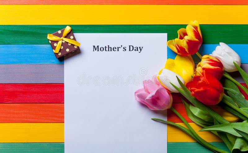 Bündel von Tulpen, von Geschenk und von Blatt des Papiers, das auf dem Tisch liegt lizenzfreies stockbild