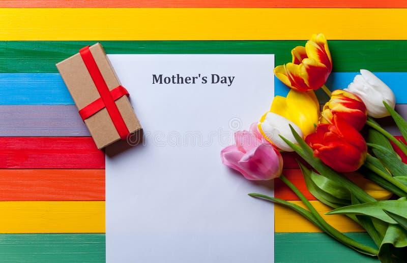 Bündel von Tulpen, von Geschenk und von Blatt des Papiers, das auf dem Tisch liegt lizenzfreie stockfotografie