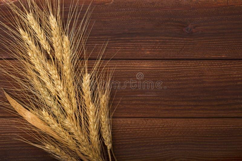 Bündel Weizenähren auf dem Holztisch Garbe Weizen über hölzernem Hintergrund stockfotografie