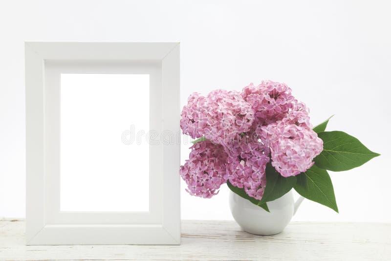 Bündeln Sie Flieder im Vase auf Holztisch- und Weißrahmenspott oben lizenzfreies stockbild