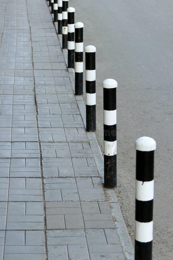Bürgersteig und Straße getrennt mit den Sicherheitsschiffspollern gemalt in Schwarzweiss lizenzfreie stockbilder
