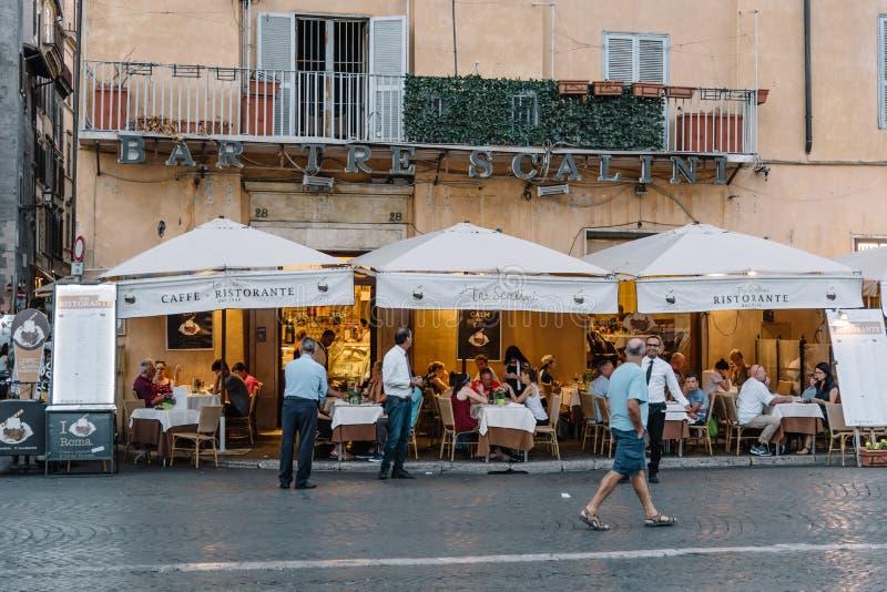Bürgersteigsrestaurant mit Touristen im römischen Quadrat ein sonnigen Sommer lizenzfreie stockbilder