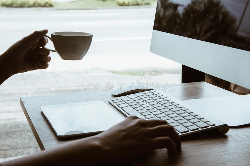 Büro, das an Bürotisch mit Computer- und Tabletten- und Kaffeetassegeschäftsbürotischarbeitsplatz arbeitet stockfotografie