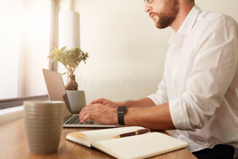 Büro des Geschäftsmannes zu Hause, das an Laptop arbeitet lizenzfreie stockbilder