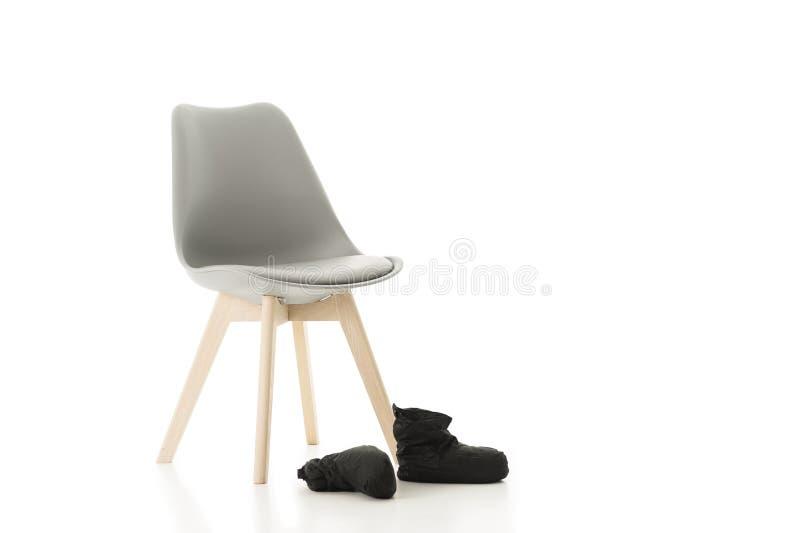 Büro-Stuhl und Paare der hinteren Schuhe auf Weiß stockfotografie