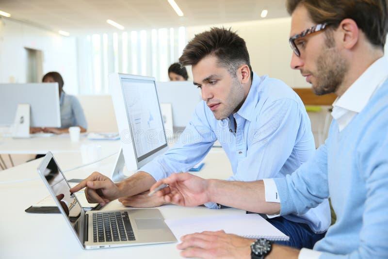 Büroangestellte, die Budget analysieren stockbilder