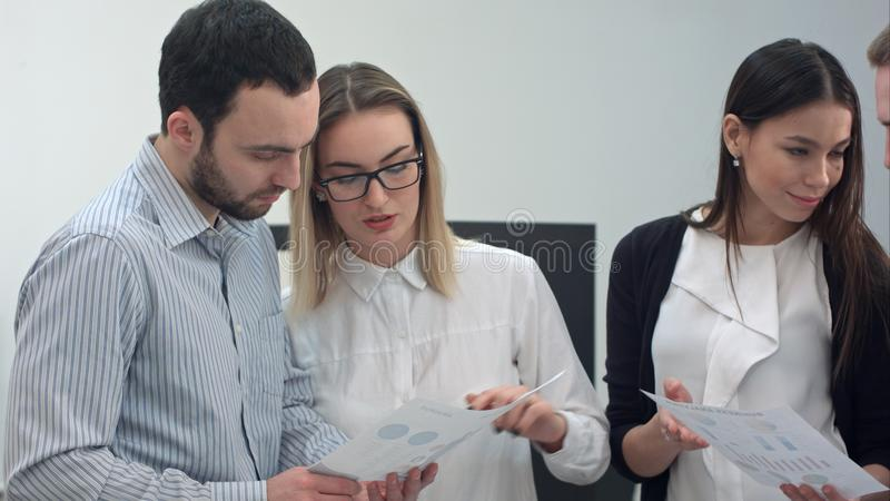 Büroangestellte, die Darstellungsmaterialien besprechen stockbilder