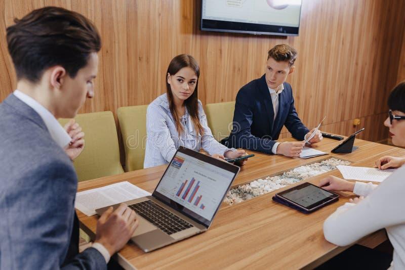 Büroangestellte halten eine Sitzung bei einem Schreibtisch für Laptops, Tabletten und Papiere, auf dem Hintergrund ein großer  lizenzfreies stockbild