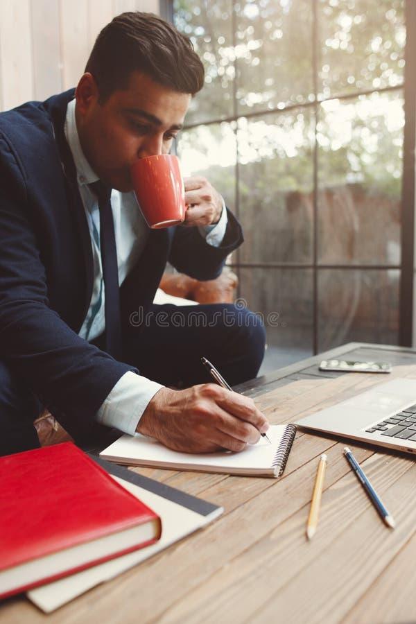 Büroangestellter, der Arbeits- und Getränkkaffee tut lizenzfreie stockbilder