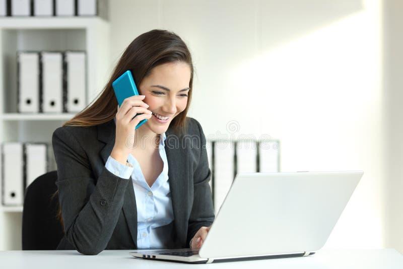 Büroangestellter, der bei einem Telefonanruf überprüft einen Laptop spricht stockbilder