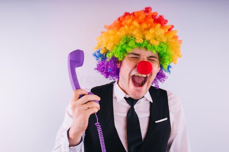Büroangestellter in der Clownperücke, Clownkonzept bei der Arbeit Geschäftsmann mit Clownperücke auf Weiß stockfoto