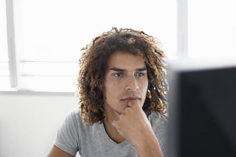Büroangestellter, der Computer-Monitor betrachtet stockfotos
