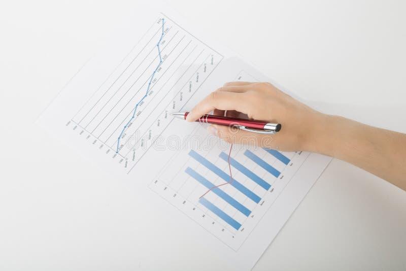 Büroangestellter, der das Diagramm mit einem Stift studiert lizenzfreies stockbild