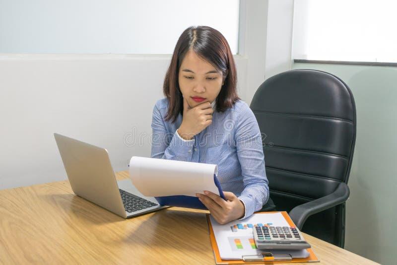 Büroangestellter, der Diagramme auf den Finanzdokumenten analysiert stockbild