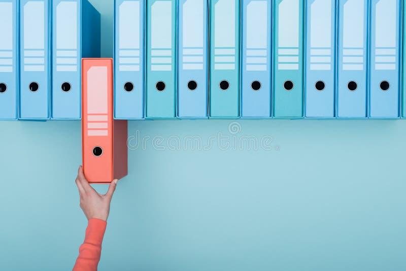 Büroangestellter, der einen Ordner im Archiv nimmt stockfotografie