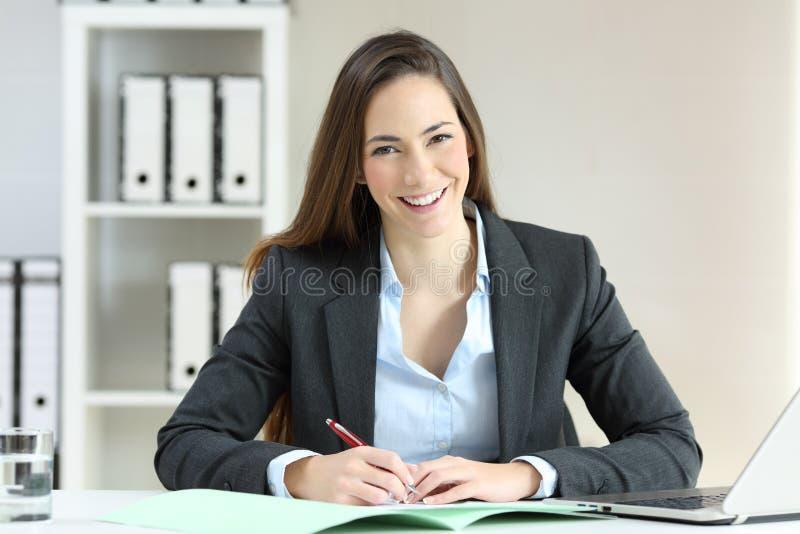 Büroangestellter, der Kamera betrachtend aufwirft stockbilder