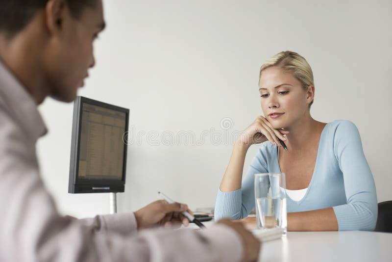 Büroangestellter und Kunde, die am Schreibtisch sitzen lizenzfreies stockfoto