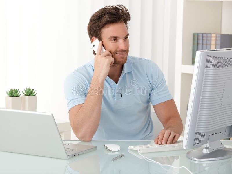 Büroangestelltkerl, der Computer und Telefon verwendet lizenzfreie stockfotografie