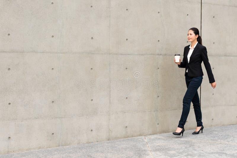 Büroangestelltmädchen, das Papierschale des heißen Espressos hält stockfotografie
