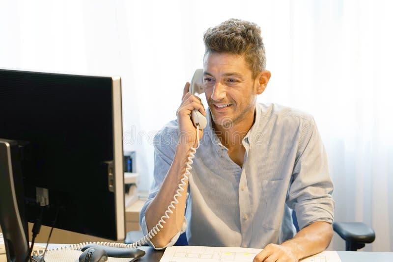 Büroangestelltmann beantwortet den Anruf lizenzfreie stockbilder