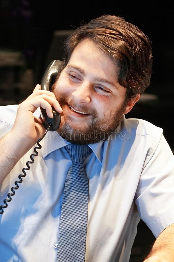 Büroangestelltmann beantwortet den Anruf stockbild