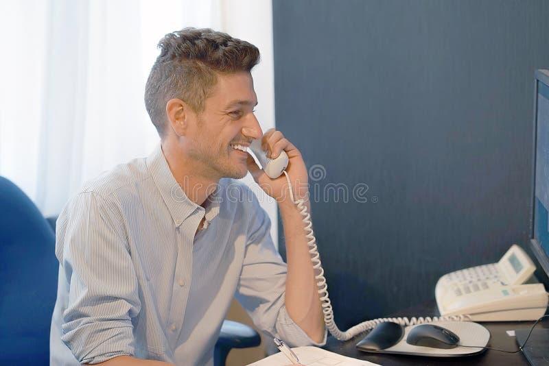 Büroangestelltmann beantwortet den Anruf lizenzfreie stockfotos