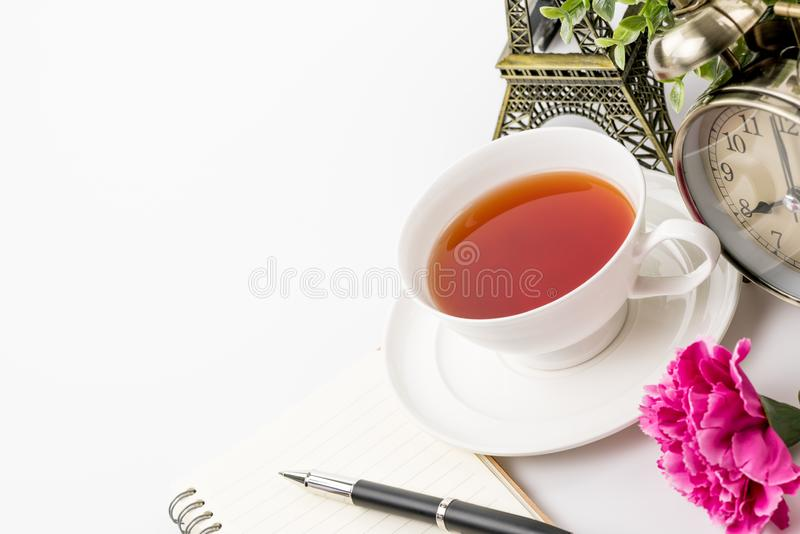 Büroarbeitsplatz mit Buchstiftuhr und Tee auf Tabelle stockfotos