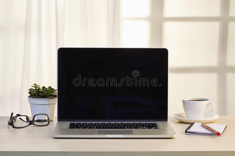 Büroarbeitsplatz mit offenem Laptop lizenzfreie stockfotos